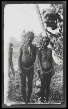 A man and wife standing next to each other on Kulumbangra Island, a large volcanic island near Gizo; both are smoking pipes; full length, full face.