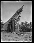 Front porch of large men's house under construction at back of beach; single-hulled canoe, with its outrigger lying detached by the side, in the foreground