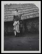 man called Mekomikwete smoking a pipe, standing next to a child outside a hut