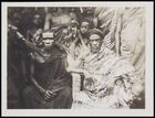2 seated males, one in a wicker chair and wearing a cloth turban, surrounded by a group: all wear body cloths