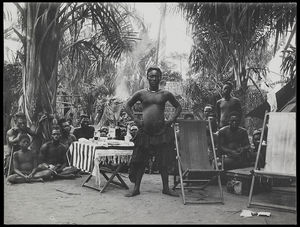 Kot aPe, the Nyimi (chief) of Mushenge (Nsheng) standing next to European style table and deck-chairs, crowd seated on ground behind him