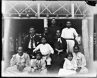 men, women and children, all South Seas teachers of the London Missionary Society, all wearing European clothing, sitting and standing posed below LMS Mission House