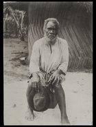 man wearing some western clothes sitting outside hut