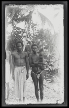 A woman holding a baby stands smoking a pipe, next to a man with a long waist cloth at Rubiana Lagoon, New Georgia Island.
