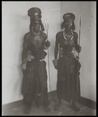 two men, one with paint around his eyes, wearing headdresses made of circular metal plate, holding spears (one with two points) standing in corner of European style room