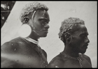 head and shoulders of two men, profile view; they wear necklaces and ear ornaments, and have their hair limed