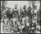group of Batwa boys lined up for the camera holding bows and arrows