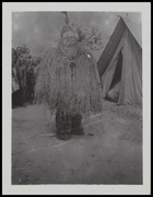 person in mask with long grass fringe by European tent