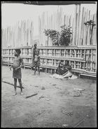 child standing in front of wooden stockade and man sitting by stockade with lengths of raffia ? used for weaving ?
