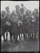 boy carrying drum and crowd of men and young boys