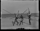 Three men wearing large painted masks, play-fighting with poles on beach (see also RAI No. 34248)