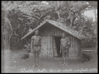 man and woman holding child standing outside small hut