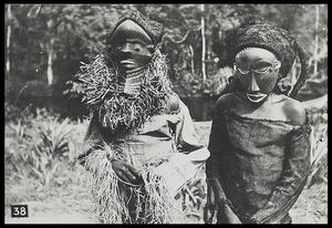 Youths (?) wearing the wooden masks Muyombo (left) and Nganga Ngombo (the diviner) (right) (the Muyombo mask is worn incorrectly in order to show it off better, it is normally worn with the face on top of the head)
