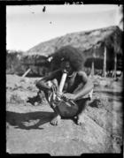 man wearing a tradecloth skirt, smokinga bamboo pipe (