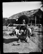 man wearing tradecloth skirt smoking a decorated bamboo pipe (