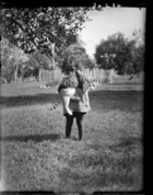 Small girl holding a cat, standing in grounds of London Missionary Society Mission House