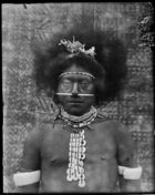 head and shoulders of man with shell jewellery and a pierced nose standing in front of barkcloth (?) backdrop