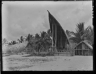 large man's house on beach, small store house on right, and another man's house on left