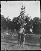 cloaked figure in elaborate feather headdress with drum