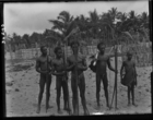 four young men, holding bows and arrows, one carrying a large string bag on a wooden pole, and a young boy carrying a large string bag, all standing on a beach with piles of cut timber (?) in background