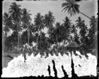 Canoe and four young men on beach (image barely visible because of damaged emuslion)