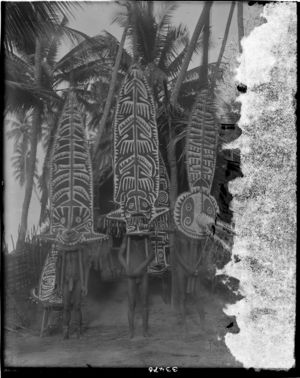 Three men wearing large painted masks, other masks behind them leaning against outside of hut (see also RAI No. 33473, 33499)