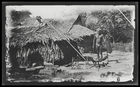 A group of cottages; a man is standing outside holding a spear and shield; Rubiana Lagoon, New Georgia Island.