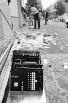 Co-op Worker Sweeping Up Debris After Riots in Notting Hill, 1976 (b/w photo)