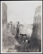 Female, 2 dogs standing among huts in compound