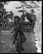 man with headdress, carrying bow and arrows and European axe, string bag over his shoulder, wearing a bark belt and bark cloth loin cloth