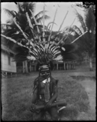 (Delena ?) man wearing large elaborate feather headdress, his nose pierced, holding a drum, sitting by danceground (?) at Nara