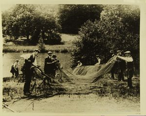 Photograph of men cleaning a fishing net, Windsor Great Park at Virginia Water