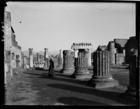 European woman looking at ruins of columns