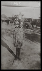 boy (?) wearing wooden mask with long grass fringe, in front of hut