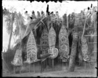 Six large painted masks leaning outside a small hut (see also RAI No. 33476, 33499)