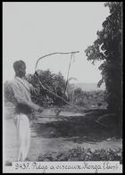 man in European clothing holding a bird trap made of bent sticks