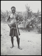 man, called Bakena, holding long wooden pipe to his mouth
