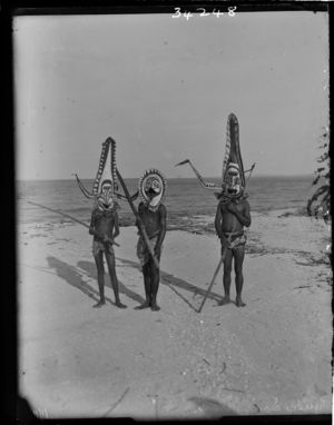 Three men in large painted masks standing on beach (see also RAI No. 34247)