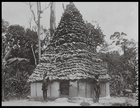 two men standing outside a tall thatched conical hut