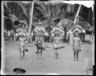 Four young men wearing jewellery and elaborate feather headdresses (clan badges), standing holding drums (see also RAI No. 33440-6) Dauncey's hat in foreground ?