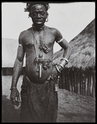 man wearing necklace with objects attached to it, standing in front of thatched hut