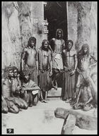 group of men standing and sitting outside entrance to a hut