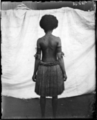 back view of woman, tattooed from head to foot, standing against white cloth backdrop (see also RAI No. 34383 ?)