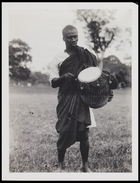 1 male dressed in tunic and body cloth carrying a small drum