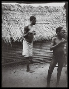 woman and young boy standing in front of thatched hut