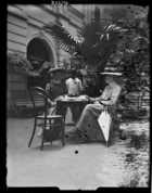 Mrs. Dauncey and another European woman, in long dresses and hats, sitting at a table having tea