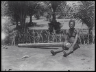 man (chief Zangi ?) sitting with one hand secured through a wooden pole, possibly as a form of punishment,