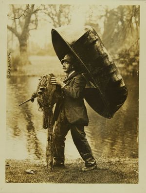 Photograph of a fisherman carrying his equipment