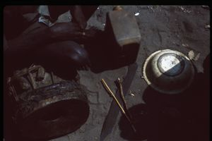 Aerial view of somebody sitting on a drum with a blade, overturned metal vessel and plastic jerrycan on the ground.