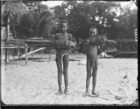 Two young boys standing on the beach holding large fish, one fish bound to a wooden pole (smoked fish ?)
